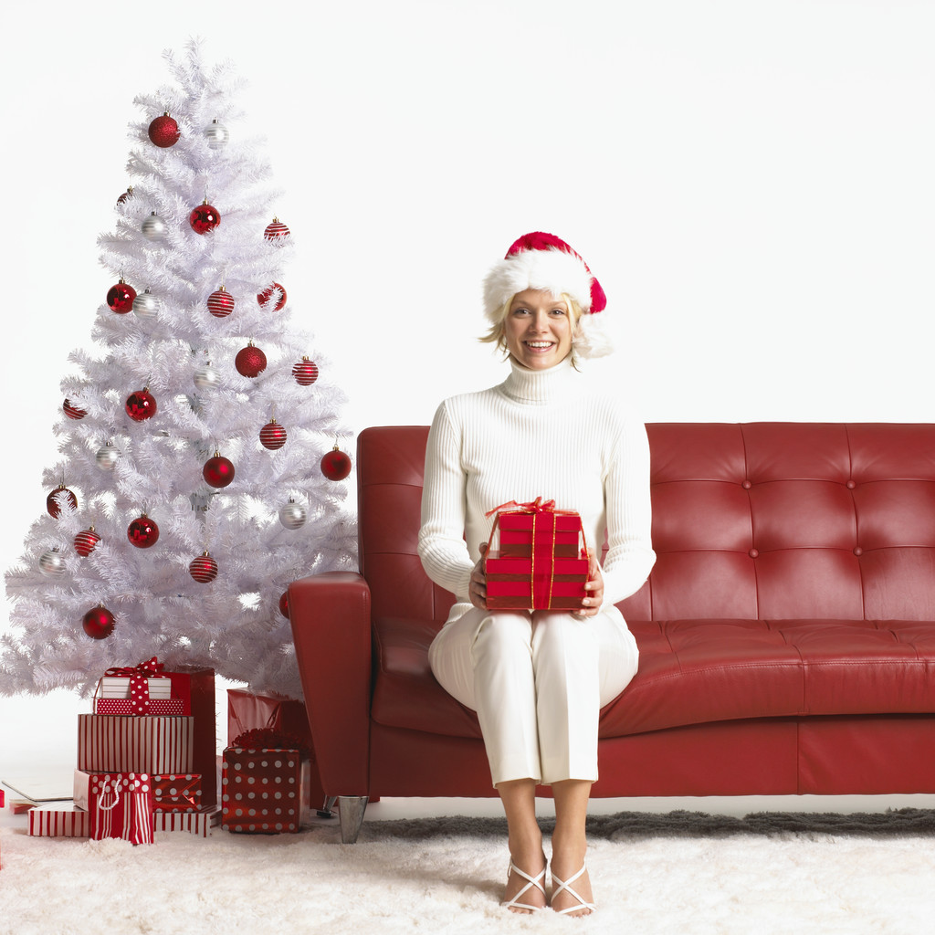 young woman sitting on couch holding christmas present and wearing santa hat image